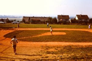 My mom pitching in a Mom v. Daughters game in Germany. Our girls BASEBALL team had played against the boys all season: came away with a 12-0 record. I am approaching the plate.